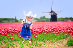 Cute girl in Dutch costume in tulips field with windmill. Adorable curly toddler girl wearing Dutch traditional national costume dress and hat playing in a field Royalty Free Stock Photography