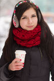 Cute girl in earplugs with coffee cup Stock Photography