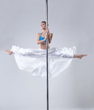 Cute girl easily performs gymnastic split on pole Stock Photos