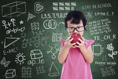 Cute girl eat apple in class Royalty Free Stock Photography