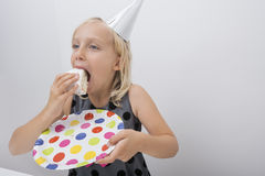 Cute girl eating birthday cake slice at home Stock Photos