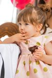 Cute Girl Eating Cake With Icing On Her Face Royalty Free Stock Photo