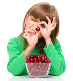 Cute girl is eating cherries. And using them as an eye, isolated over white Stock Photography