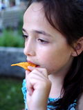 A  Cute Girl Eating Chips. A cute young girl enjoying a tasty snack Stock Photography