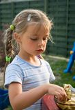 Cute girl eating chocolate. Cute young blond girl in garden eating white chocolate Stock Photos
