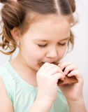 Cute girl is eating chocolate candy Stock Photo