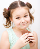Cute girl is eating chocolate candy Royalty Free Stock Photo