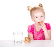 Cute girl eating a chocolate chip cookie. A cute little girl eating a chocolate chip cookie isolated on a white background Stock Photography