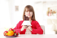 Cute girl eating chocolate Stock Image