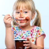 Cute girl eating chocolate yogurt. Stock Photography