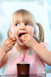 Cute girl eating chocolate yogurt with hands. Stock Photos