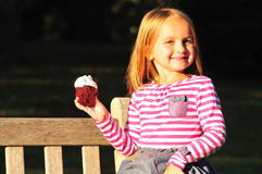 Cute girl eating cupcake stock images
