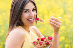 Cute girl eating healthy cereal breakfast outdoors. Close up face shot of attractive young woman eating healthy crispy whole grain cereal breakfast outdoors stock image