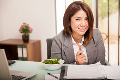 Cute girl eating a healthy lunch. Portrait of a beautiful young business woman enjoying a fresh salad while working at the office Royalty Free Stock Photography