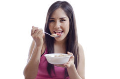 Cute girl eating healthy. Young beautiful woman in sporty outfit eating cereal from a bowl Royalty Free Stock Photo