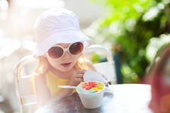 Cute girl eating ice cream Stock Images