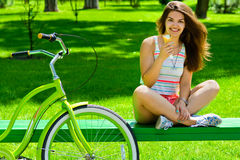 Cute girl eating ice cream after cycling cruiser.  Royalty Free Stock Photography