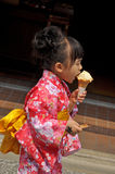Cute girl eating ice cream. KYOTO, JAPAN - APRIL 10, 2014 : Cute girl in Japanese kimono dress eating ice cream in Kyoto, Japan Royalty Free Stock Image