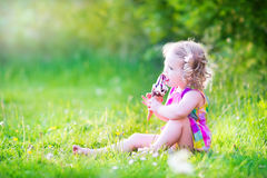 Cute girl eating ice cream in the sunny garden Stock Photo