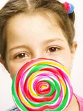 Cute girl eating lollipop. Close Up of Young girl eating a Lollipop on white background stock photo