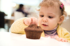 Cute girl eating muffins in cafe Stock Photography