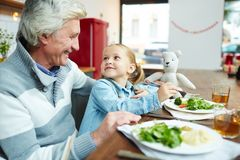 Breakfast at home. Cute girl eating organic food and talking to her grandfather by breakfast Royalty Free Stock Photos