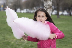 Cute girl eating pink cotton candy. Selective focus Stock Photo