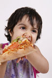 Cute girl eating pizza Stock Images