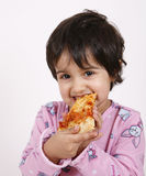 Cute girl eating pizza slice Stock Images