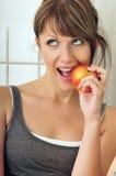 Cute girl eating a red apple. Cute brunette girl eating a red apple stock images