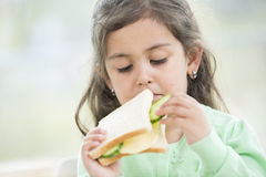 Cute girl eating sandwich at home Royalty Free Stock Photography