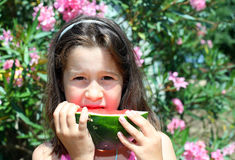 Cute girl eating a slice of watermelon. Cute girl eating a slice of ripe watermelon in summer Stock Images