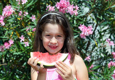 Cute girl eating a slice of watermelon. Cute girl eating a slice of ripe watermelon in summer Royalty Free Stock Photos