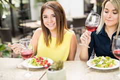 Cute girl eating with some friends. Portrait of a gorgeous young Latin women eating and drinking wine with some female friends Stock Images