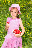 Cute girl eating strawberries Royalty Free Stock Images