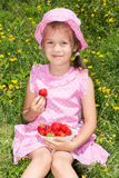Cute girl eating strawberries Royalty Free Stock Image