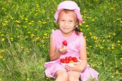 Cute girl eating strawberries Royalty Free Stock Photos