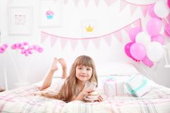 Cute girl eating tasty cake while lying on bed  in room decorated for birthday party. Cute girl eating tasty cake while lying on bed in room decorated for Royalty Free Stock Photography