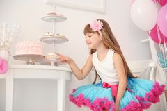 Cute girl eating tasty cakes in room decorated. For birthday celebration Royalty Free Stock Images