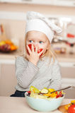 Cute girl eating tomato while cooking salad in Royalty Free Stock Photo