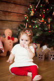 Cute girl eating twisted Christmas candy cane Stock Image
