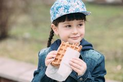 Cute girl eating waffle in the yard stock photography