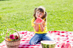 Cute girl eating watermelon on the grass in. Cute child girl eating watermelon on the grass in summertime Royalty Free Stock Photography