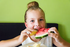 Cute girl eating watermelon and melon Stock Photo
