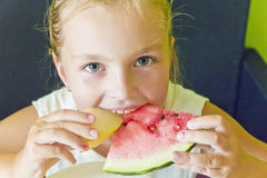 Cute girl eating watermelon and melon Royalty Free Stock Photos