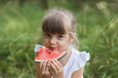 Cute girl eating watermelon in summer stock photography