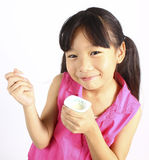 Cute girl eating yogurt. Isolated on white Stock Photography