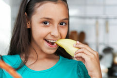 Cute girl eats an pepper Stock Images