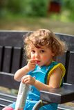 Cute girl eats snacks in park stock photos