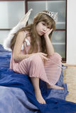 Cute girl eight years old wearing angel wings sad. Little cute girl eight years old wearing angel wings sad after festival Stock Photo